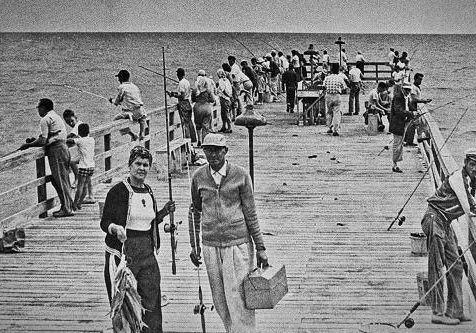 black and white photo of fishermen on the pier